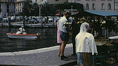 Lake Garda 1968: people walking in an outdoor market Stock Footage