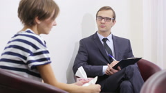 Pretty male psychiatrist looking at patient during her visit Stock Footage