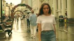 Beautiful brunnete girl with long hair walks in the street after summer rain - stock footage