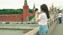 Beautiful young caucasian brunette girl taking photos of Moscow Kremlin - stock footage