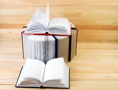 Open book, stack of hardback books on wooden table. Back to school. Copy space Stock Photos
