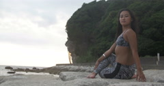 Tanned Asian Japanese girl doing Yoga on rocks beach side - stock footage