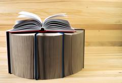 Open book, stack of hardback books on wooden table. Back to school. Copy space - stock photo