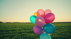 Little girl child kid with balloons outdoors on sky and field background. RAW - stock footage