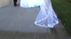 Bridal veil dragged on the concrete driveway behind the woman dressed in white Stock Footage