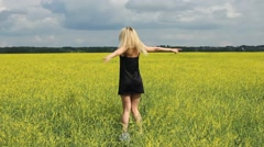 Happy woman in black dress jumps to the sky in the yellow meadow Stock Footage
