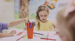 Little girl drawing with colored pencils on paper Stock Footage