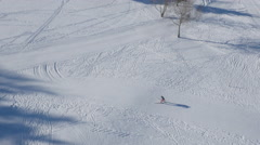 Aerial of skier skiing on ski slope on a sunny winter day Stock Footage