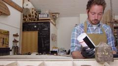 Man Glueing Custom Surfboard In Workshop Shot On RED Camera Stock Footage