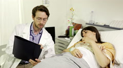 Doctor showing test results to woman lying in hospital bed dolly shot 4K Stock Footage