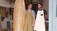 Carpenter And Apprentice With Surfboard Shot On RED Camera Stock Footage