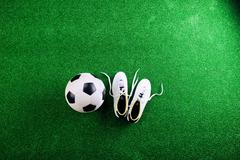 Soccer ball and cleats against green artificial turf, studio sho Stock Photos