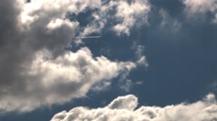 Jumbo jet coming out speed between white and fluffy clouds that go with speed - stock footage