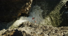 Two mountaineers hanging over a river and waterfall in a deep canyon Stock Footage