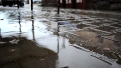 Splashes of water falling in puddles formed on a driveway slabs situated near Stock Footage