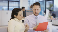 4K Business man & woman having a discussion in modern corporate office - stock footage
