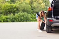 Woman changes the wheel of car on a road Stock Photos