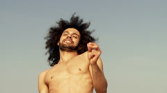 Cool happy man dancing in front of the ocean in summer slow motion closeup - stock footage