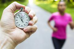 Stopwatch Timer and Young Woman Running Stock Photos
