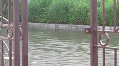 Flooded road view through the gate and the car rides Stock Footage
