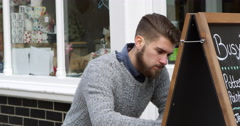 Man Writing On Noticeboard Outside Coffee Shop Shot On R3D Stock Footage