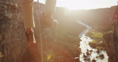 Rock climbers ascending ropes in front of sun flare above a canyon Stock Footage