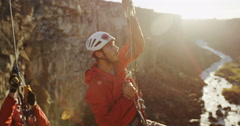 Reveal of rock climbers climbing out of a canyon above a river with a sun flare Stock Footage