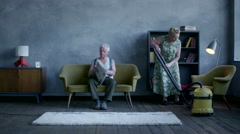 Elderly woman vacuuming the floor, and an elderly man reading a newspaper and Stock Footage