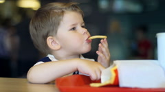 Funny little boy eating french fries in restaurant Stock Footage