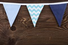 Party triangle bunting flags hanging on the rope. On the old wooden backgroun Stock Photos