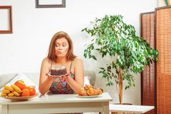 Fat woman sitting at table home Stock Photos