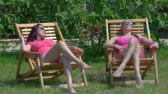 Two young relaxed women sitting on green lawn in house garden - stock footage