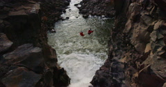 Rock climbers hanging off of ropes over a raging waterfall in slow motion Stock Footage