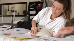 Female Student Lying On Bed Studying With Notes And Files Stock Footage