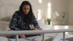 Female Student Sitting On Bed Studying With Notes And Laptop Stock Footage