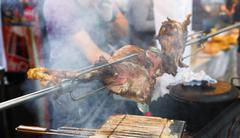 Lamb leg roasted at spit, meat barbecue Stock Photos