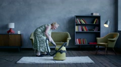 happy elderly woman dancing with a vacuum cleaner, home fun - stock footage