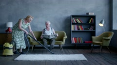 Elderly woman vacuuming the floor, and an elderly man reading a newspaper Arkistovideo