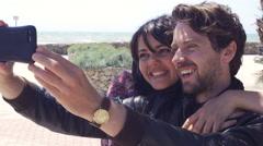 Cute happy couple in love taking selfie in front of the ocean 4K - stock footage