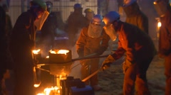 Workers Are Pouring Out Liquid Metal Carefully Silhouettes Lit by Orange Flame Stock Footage