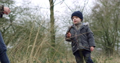 Boy Playing With Stick On Walk With Family Shot On R3D Stock Footage