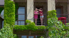 Two young women on balcony overgrown with creeping plants - stock footage