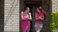 Two young women friends standing on balcony and talking in summer - stock footage