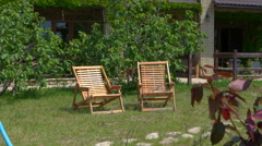 Two outdoor wooden lawn chairs in private house garden on a summer day Stock Footage