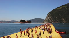 People walking along The Floating Piers work of art, made by artist Christo Stock Footage