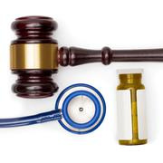 Judge gavel, pills bottle and stethoscope on white backround Stock Photos
