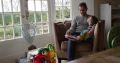 Father Sits In Chair At Home Reading Book To Son Shot On R3D Stock Footage