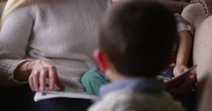 Mother Sits In Chair And Reads Book To Sons Shot On R3D Stock Footage