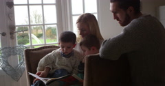 Family Sits In Chair And Reads Book Together Shot On R3D Stock Footage