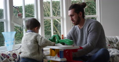 Father And Son Playing With Toy Garage In Window Seat, Shot on R3D Stock Footage